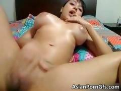 Busty oriental floozy rubbing wet shaved